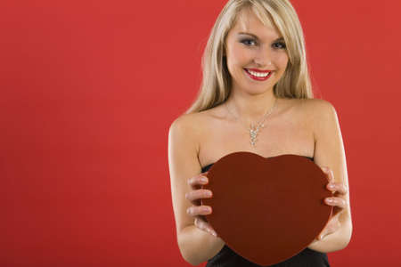 Beautiful woman in black dress, holding heart-shaped box of chocolates. Smiling and looking at camera. Front view Stock Photo - 2610471
