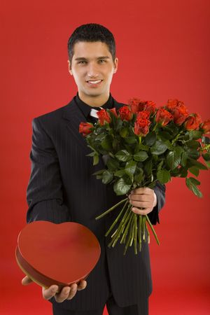 Handsome businessman, with bouquet of roses and box of chocolates in hands. Smiling and looking at camera. Front view Stock Photo - 2610456