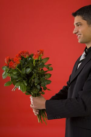 Handsome and smiling businessman with bouquet of roses in hands. Side view Stock Photo - 2610455