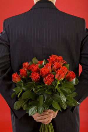 Businessman holding bouquet of roses behind his back. We dont see his face. Rear view  photo