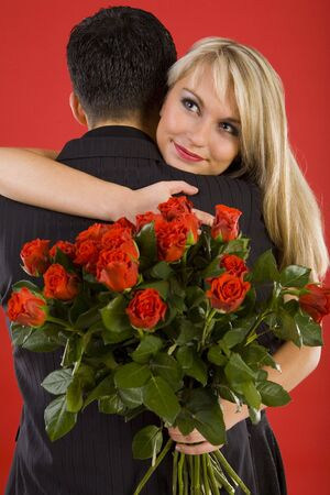 Young couple in happy hug. Woman is holding bouquet of roses, smiling and looking at something Stock Photo - 2610443