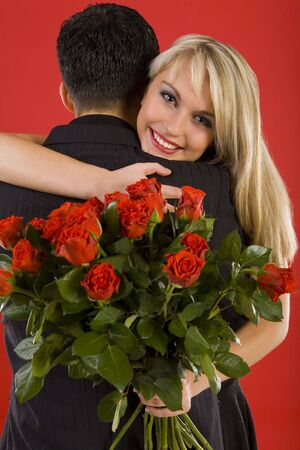 Young couple in happy hug. Woman is holding bouquet of roses, smiling and looking at camera Stock Photo - 2610432