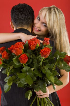 Young couple in happy hug. Woman is holding bouquet of roses, smiling and looking at camera Stock Photo - 2610430