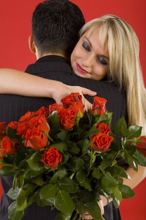 Young couple in happy hug. Woman is holding bouquet of roses, smiling and have closed eyes Stock Photo - 2610444