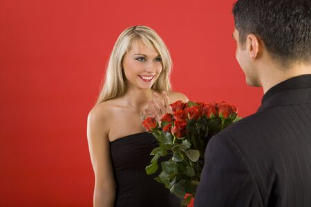 Young man in suit is giving flowers to beautiful, smiling woman. The man is standing back Stock Photo - 2610481