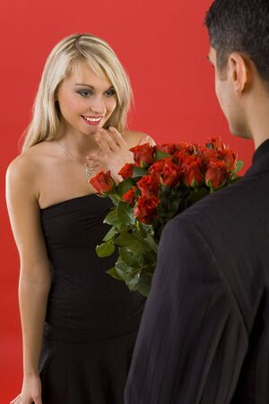 Young man in suit is giving flowers to beautiful, smiling woman. The man is standing back Stock Photo - 2610484