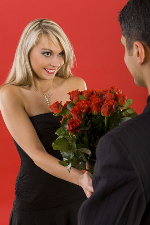 giving back: Young man in suit is giving flowers to beautiful, smiling woman. The man is standing back Stock Photo