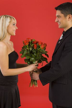 Handsome man in suit is giving beautiful woman bouquet of roses. They are both smiling. Side view  Stock Photo - 2610458