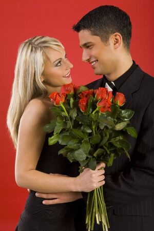 Young couple in happy hug. Womanan is holding bouquet of roses, smiling and looking at man. Side view Stock Photo - 2610447