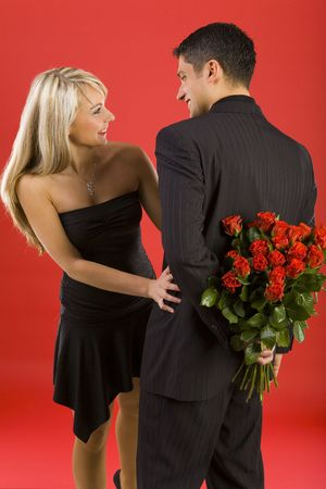 Young man in suit is hiding flowers before beautiful, smiling woman. The man is standing back Stock Photo - 2610446
