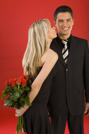 Young, happy couple. Woman is holding bouquet of roses and kissing man. The man is smiling and looking at camera Stock Photo - 2610429