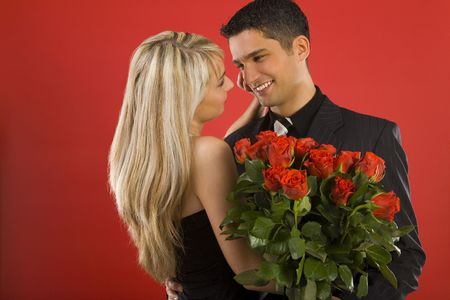 Young couple in happy hug. Man is holding bouquet of roses, smiling and looking at woman. Side view Stock Photo - 2610437