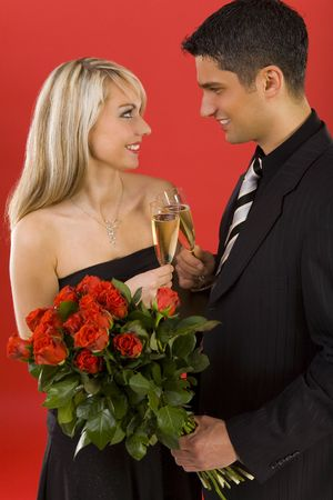 Young couple raising toast. Manan is holding bouquet of roses. They are both smiling and looking at each other. Side view Stock Photo - 2610445