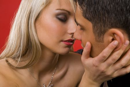 tender passion: Young, kissing couple. They are looking very passionately. Woman is holding mans face  Stock Photo