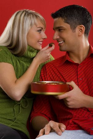 Young enamoured couple. Woman is feeding man by chocolate and smiling. Front view photo
