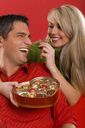 enamoured: Young enamoured couple. Woman is feeding man by chocolate and smiling. Front view