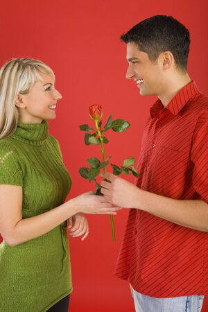 Handsome man is giving beautiful woman one rose. They are both smiling. Side view Stock Photo - 2610419