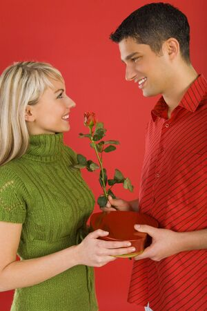 Handsome man is giving beautiful woman on erose and box of chocolates. They are both smiling. Side view Stock Photo - 2610425
