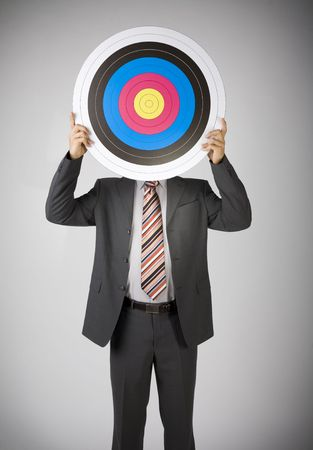 Businessman holding archery target. Covering face. Front view, gray background photo