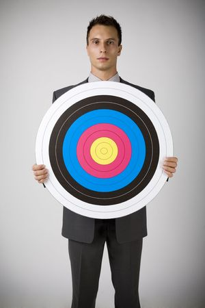 Young businessman holding archery target. Seusly looking at camera. Front view, gray background Stock Photo - 2610502