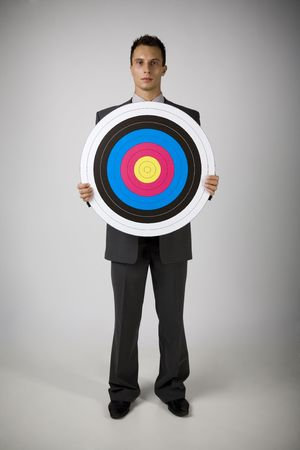 the whole body: Young businessman holding archery target. Seriously looking at camera. Front view, whole body. Gray background