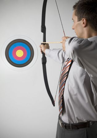 aiming: Businessman holding bow and shooting to archery target. Rear view, gray background Stock Photo
