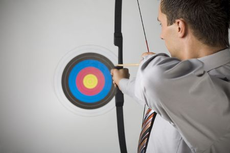 archer: Businessman holding bow and shooting to archery target. Rear view, gray background Stock Photo