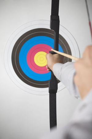 shooting target: Businessman holding bow and shooting to archery target. Rear view, gray background Stock Photo
