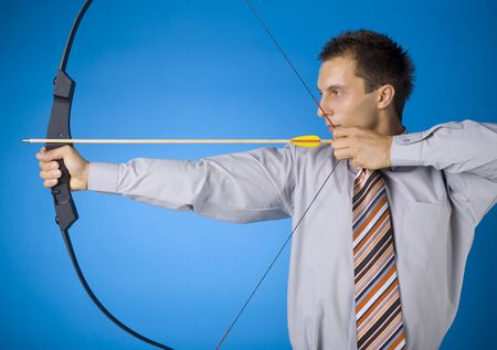 archer: Young businessman holding bow and shooting to target. Blue background Stock Photo