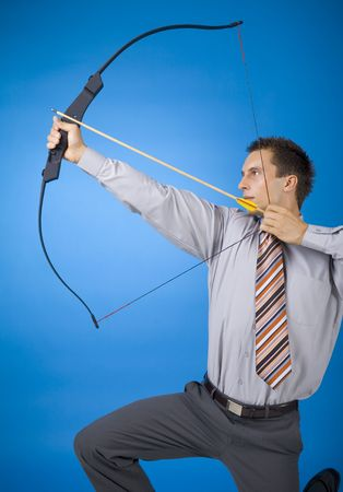 Young businessman holding bow and shooting to target. Blue background Stock Photo