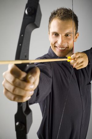 Young, elegant man in black shirt holding bow. Smiling and shooting to target. Gray background, front view Stock Photo - 2610473