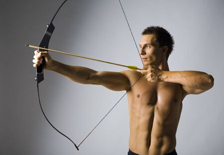 Young,  man holding bow and shooting to target. Gray background