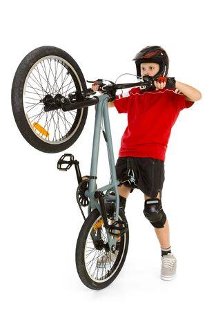 ni�os en bicicleta: Cosecha joven del motorista encima de la rueda delantera su BMX. �l  s en casco y kneepad. Aislado en el fondo blanco.