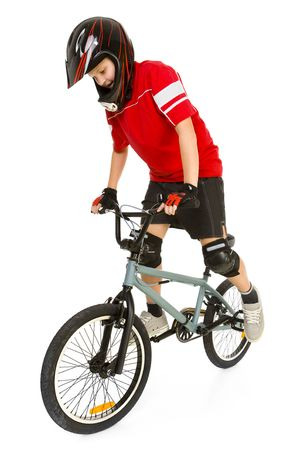 Young boy in red T-shirt cycling on BMX. Hes maintain equilibrium. Isolated on white background. photo