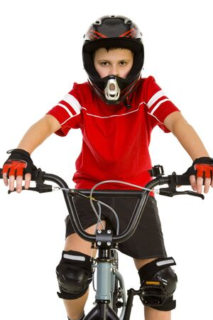 Young boy in helmet and protection kit sitting on BMX and looking at camera. Front view. White background. photo
