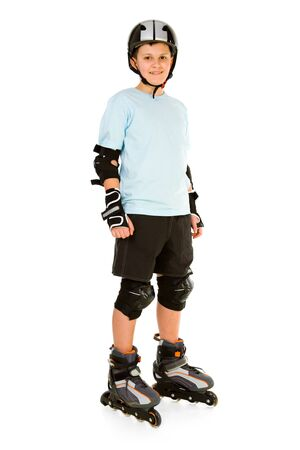 Young, happy roller boy in protection kit standing and looking at camera. Front view. Isolated on white background. photo