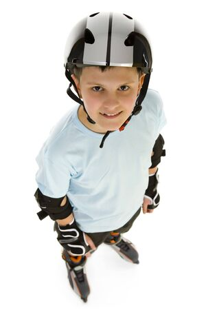 extreme angle: Young, happy roller boy in protection kit standing and looking at camera. High angle view. Isolated on white background.
