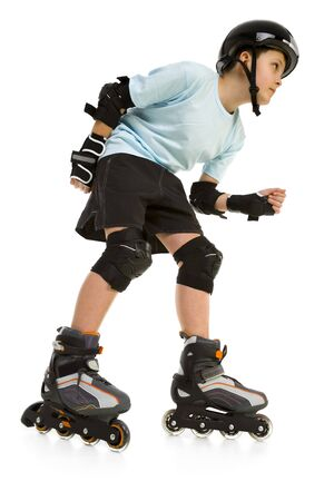 Young skater boy ready to ride on roller skates. Hes looking at something. Side view. Isolated on white background.