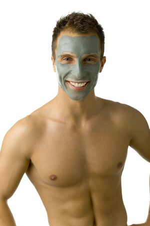 Young, handsome man with green mask on face. Smiling and looking at camera. White background, front view photo