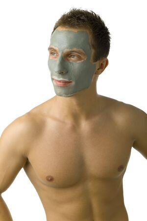 Young, handsome man with green mask on face. Smiling and looking at left. White background, front view photo