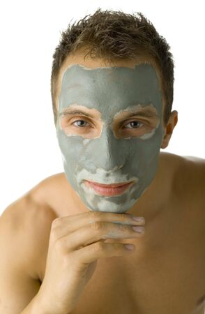 Young, handsome and  man with green mask on face. Smiling, thinking of something and looking at camera. White background, front view photo