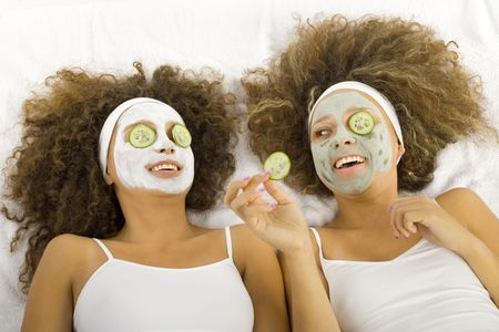 antiaging: Happy twins with anti-aging face masks. Cucumber slices covering theirs eyes. Therre lying on towels. Stock Photo