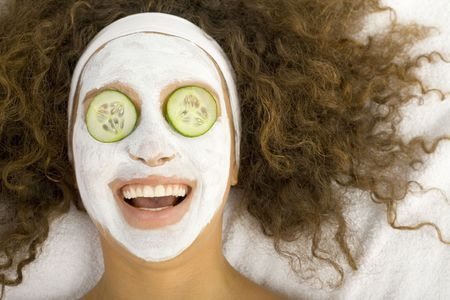 purifying: Young happy woman with white purifying mask and cucumbers slices on eyes. Stock Photo