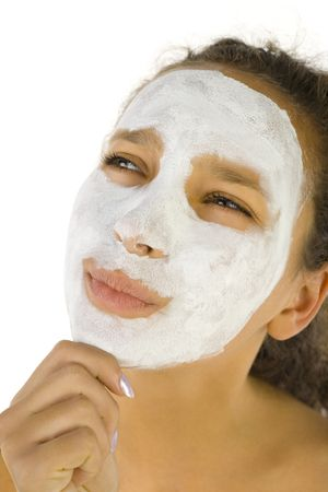 antiaging: Thoughtful girl with purifying mask on face. Shes on white background