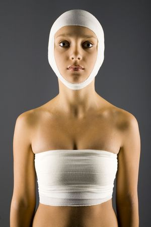 hospitalization: Young, unhappy and beautiful woman with bandage on head. Looking at camera. Front view, gray background Stock Photo