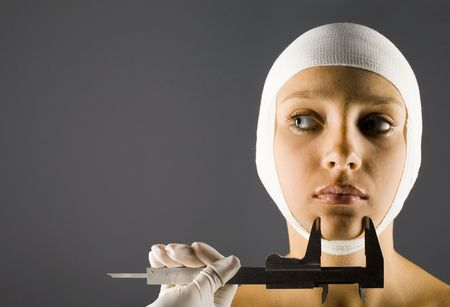 hospitalization: Young, beautiful woman with bandage on head. Somebody in rubber glove holding calliper. Front view, gray background