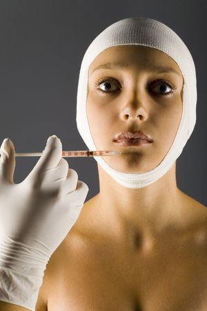 Young, beautiful woman with bandage on head. Somebody is injecting something in hers lips. Front view, gray background photo