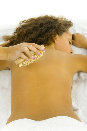 rubdown: Young woman taking massage. Shes lying on towel. Stock Photo
