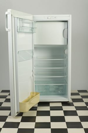 Opened, empty fridge, standing on black and white floor. Front view photo