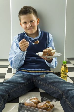 glutton: Smiling boy sitting on the floor with cake on dessert plate. Front view. Looking at camera.